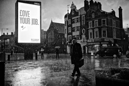 "Love Your Job. A heavy downpour of rain soaks pedestrians and a businessman, as they pass an illuminated advertising sign saying ""Love Your Job"". Hammersmith, London. January 14, 2011. Photo: ©Edmond Terakopian"