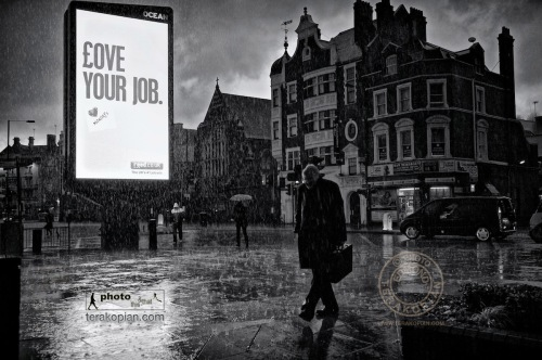 "Love Your Job: A heavy downpour of rain soaks pedestrians as they pass an illuminated advertising sign saying ""Love Your Job"". Hammersmith, London. January 14, 2011. Photo: ©Edmond Terakopian"