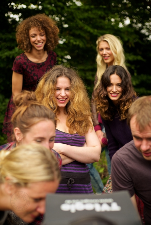 Director Rebecca Gower, surrounded by the models, all have a look at the latest take on a field monitor. New Look behind the scenes shoot of their Autumn / Winter 2013 collection advertising film by Cherry Duck. Walnuts Farm, Old Heathfield, East Sussex, UK. August 22, 2013. Photo: ©Edmond Terakopian