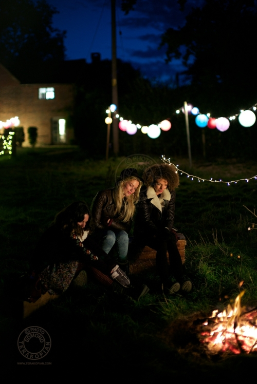 Models (L-R) Lizzie Bowden, Sophie Harries and Leanne Pollock relax by a bonfire. New Look behind the scenes shoot of their Autumn / Winter 2013 collection advertising film by Cherry Duck. Walnuts Farm, Old Heathfield, East Sussex, UK. August 22, 2013. Photo: ©Edmond Terakopian
