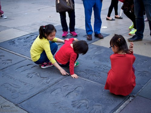 Visitors at the Chinese Theatre forecourt featuring handprints, footprints and signatures of iconic celebrities. The young visitors check out the Harry Potter imprints. Hollywood Boulevard, Hollywood, California. January 16, 2014. Photo: Edmond Terakopian