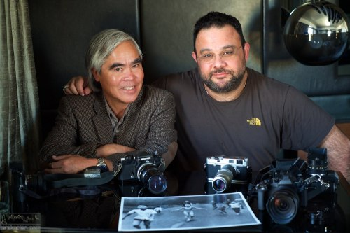 "(L-R) AP photographer Nick Ut, author of the Pulitzer Award winning ""Napalm Girl"" photograph (shown) from the Vietnam War and Edmond Terakopian. Image shows some of Nick Ut's cameras used during the Vietnam War and more modern cameras; on the right is Edmond Terakopian's Olympus OM-D E-M1. Thompson Beverly Hills, LA, California, USA. January 18, 2014. Photo: Edmond Terakopian (self timer image)"