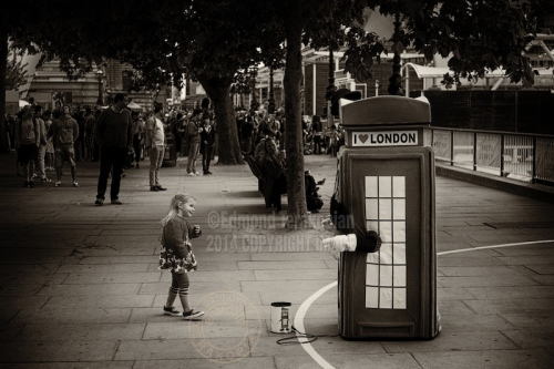 A street performer dressed as a telephone box entertains a young passer by. June 27, 2013. Photo: ©Edmond Terakopian
