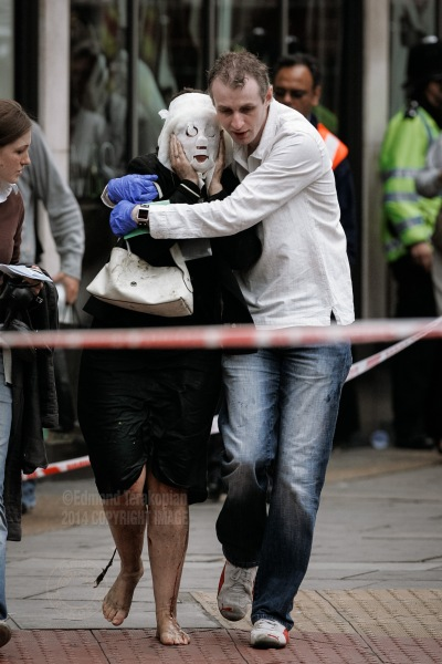 Paul Dadge leads Davinia Turrell (now Davinia Douglass) away from Edgware Road tube station after a suicide bomb attack in which she suffered burn injuries, resulting in the need for a face mask. The bomber blew himself up on a train at the station, killing seven passengers - one of four coordinated attacks on London's public transport system during the morning rush hour. The bombs exploded within 50 seconds of each other on London Underground trains, and the fourth bomb occurred on a bus less than an hour later. The explosions resulted in some 56 deaths (including those of the four bombers) and 700 injuries. Surveillance video footage showed that the four men had been working together. Intelligence services have claimed links between the bombers and al-Qaeda. Edgware Road underground station, London, United Kingdom. July 07, 2005. Photo: Edmond Terakopian