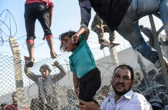 "A Syrian child fleeing the war is lifted over border fences to enter Turkish territory illegally, near the Turkish border crossing at Akcakale in Sanliurfa province on June 14, 2015. Turkey said it was taking measures to limit the flow of Syrian refugees onto its territory after an influx of thousands more over the last days due to fighting between Kurds and jihadists. Under an ""open-door"" policy, Turkey has taken in 1.8 million Syrian refugees since the conflict in Syria erupted in 2011. AFP PHOTO / BULENT KILIC / AFP / BULENT KILIC"