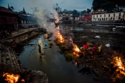 8—Kathmandu, Nepal, Tuesday, April 28, 2015: Flames rise from burning funeral pyres during the cremation of earthquake victims, at the Pashupatinath temple on the banks of Bagmati river on April 28, 2015 in Kathmandu, Nepal. On the 25th of April, just before noon local time, as farmers were out in fields and people at home or work, a devastating earthquake struck Nepal, killing over 8,000 people and injuring more than 21,000 according to the United Nations Office for the Coordination of Humanitarian Affairs. Homes, buildings and temples in Kathmandu were destroyed in the 7.8 magnitude quake, which left over 2.8 million people homeless, but it was the mountainous districts away from the capital that were the hardest hit. Villagers pulled the bodies of their loved ones from the rubble by hand and the wails of grieving families echoed through the mountains, as mothers were left to bury their own children. Over the following weeks and months, villagers picked through ruins desperate to recover whatever personal possessions they could find and salvage any building materials that could be reused. Despite relief teams arriving from all over the world in the days after the quake hit, thousands of residents living in remote hillside villages were left to fend for themselves, as rescuers struggled to reach all those affected. Multiple aftershocks, widespread damage and fear kept tourists away from the country known for its searing Himalayan peaks, damaging a vital climbing and trekking industry and compounding the recovery effort in the face of a disaster from which the people of Nepal continue to battle to recover.