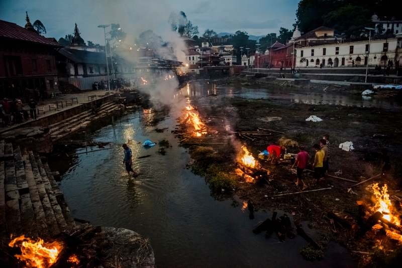 8—Kathmandu, Nepal, Tuesday, April 28, 2015:Flames rise from burning funeral pyres during the cremation of earthquake victims, at the Pashupatinath temple on the banks of Bagmati river on April 28, 2015 in Kathmandu, Nepal. On the 25th of April, just before noon local time, as farmers were out in fields and people at home or work, a devastating earthquake struck Nepal, killing over 8,000 people and injuring more than 21,000 according to the United Nations Office for the Coordination of Humanitarian Affairs. Homes, buildings and temples in Kathmandu were destroyed in the 7.8 magnitude quake, which left over 2.8 million people homeless, but it was the mountainous districts away from the capital that were the hardest hit. Villagers pulled the bodies of their loved ones from the rubble by hand and the wails of grieving families echoed through the mountains, as mothers were left to bury their own children. Over the following weeks and months, villagers picked through ruins desperate to recover whatever personal possessions they could find and salvage any building materials that could be reused. Despite relief teams arriving from all over the world in the days after the quake hit, thousands of residents living in remote hillside villages were left to fend for themselves, as rescuers struggled to reach all those affected. Multiple aftershocks, widespread damage and fear kept tourists away from the country known for its searing Himalayan peaks, damaging a vital climbing and trekking industry and compounding the recovery effort in the face of a disaster from which the people of Nepal continue to battle to recover.