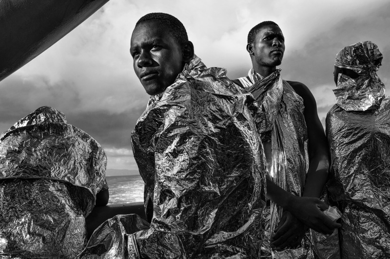 After spending two days and two nights sailing on the Mediterranean Sea on the deck of the M.S.F. (Médecins Sans Frontières - Doctors Without Borders) search and rescue ship Bourbon Argos, rescued migrants - still wrapped in their emergency blankets - catch sight of the Italian coast for the first time soon after dawn. 23 August 2015