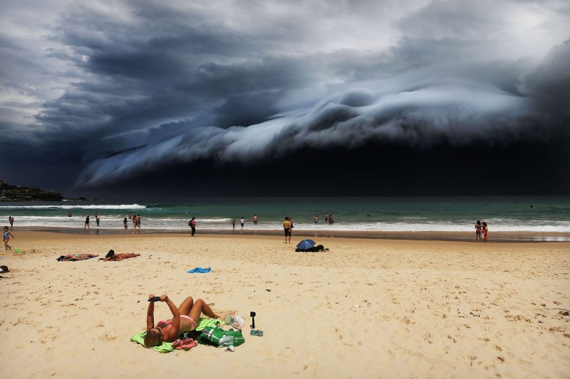 """Sunbather oblivious to the ominous shelf cloud approaching -  on Bondi beach. A massive """"cloud tsunami"""" looms over Sydney in a spectacular weather event seen only a few times a year.The enormous shelf cloud rolled in from the sea, turning the sky almost black and bringing violent thunderstorms in its wake."""